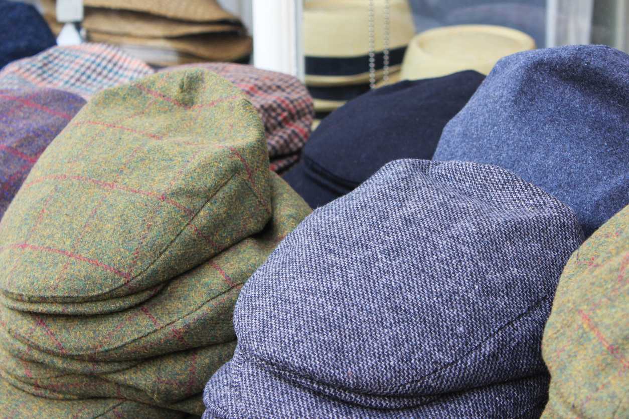 Variation men's newsboy cap stack in clothing store. Large group of hats are placed in a row, stack together. Many different textured & pattern.