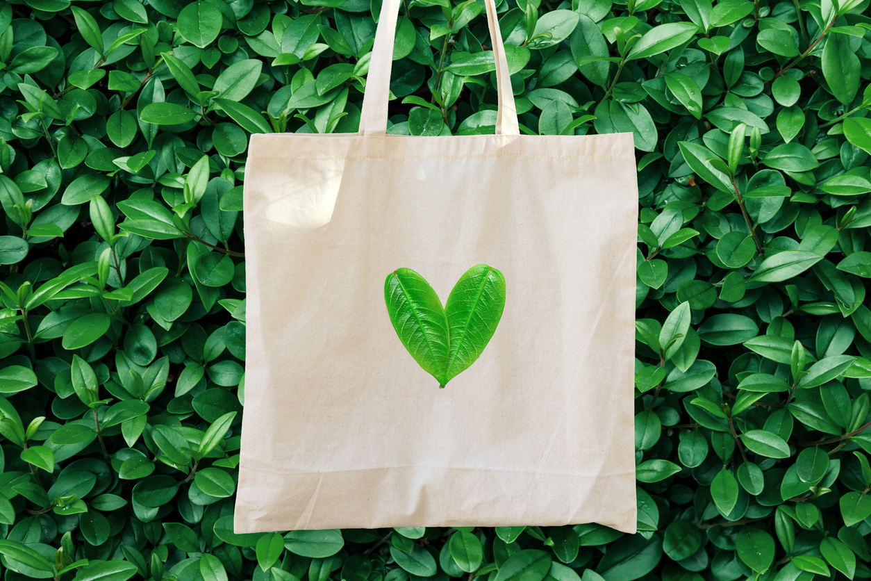 Blank white mockup linen cotton tote bag on green bush trees foliage background. Heart logo from leaves. Nature friendly style. Environmental conservation recycling plastic free