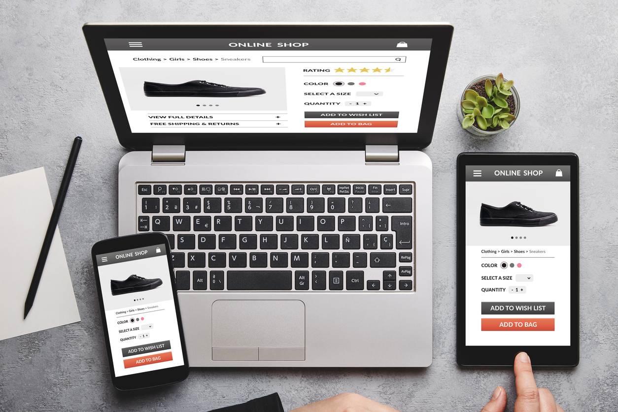 Online shop concept on laptop, tablet and smartphone screen over gray table. All screen content is designed by me. Flat lay