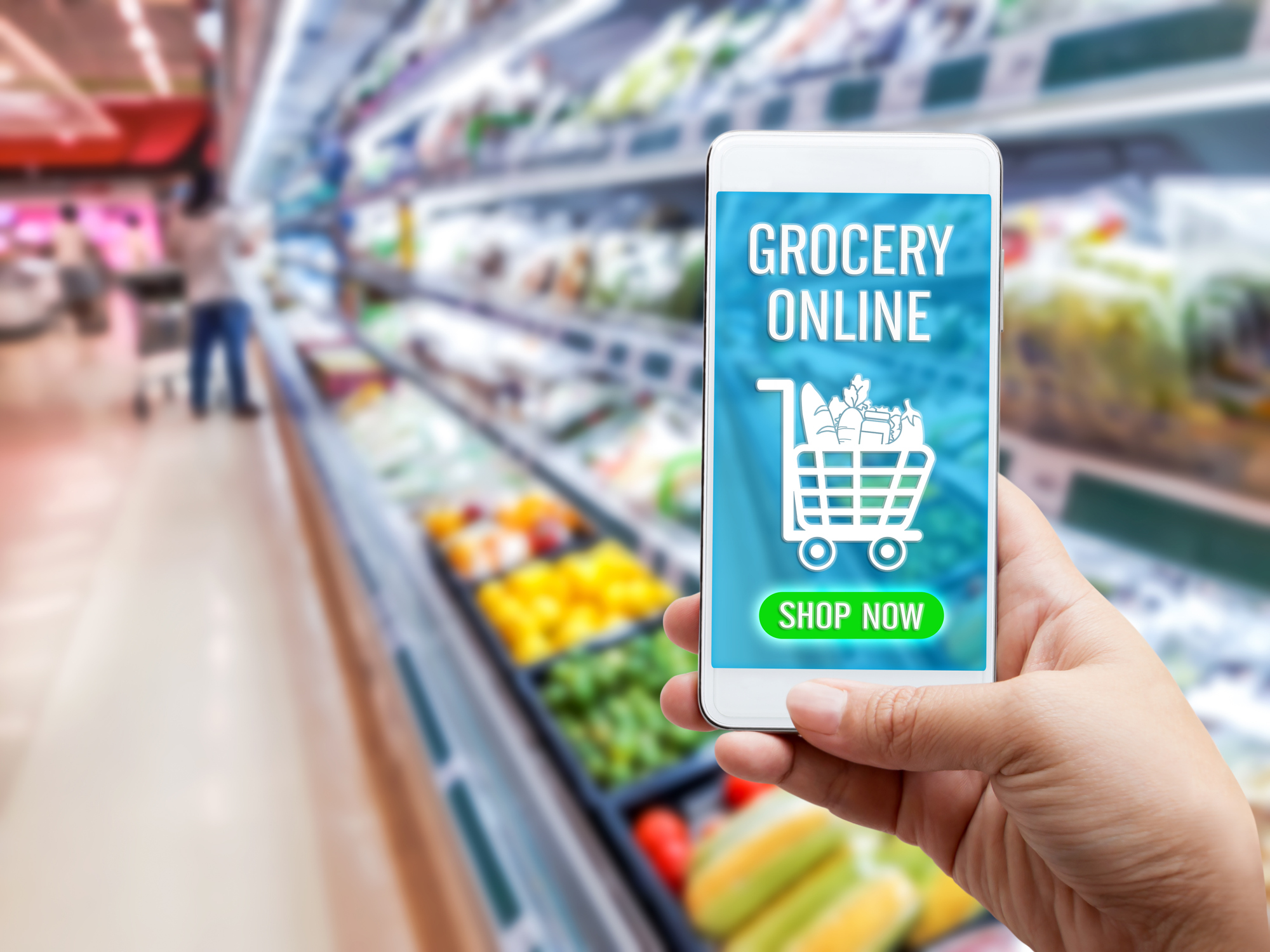 Online grocery shopping concept: Woman hand holding smart phone for ordering food onscreen with icon media on supermarket background. Business and technology for lifestyle in city.
