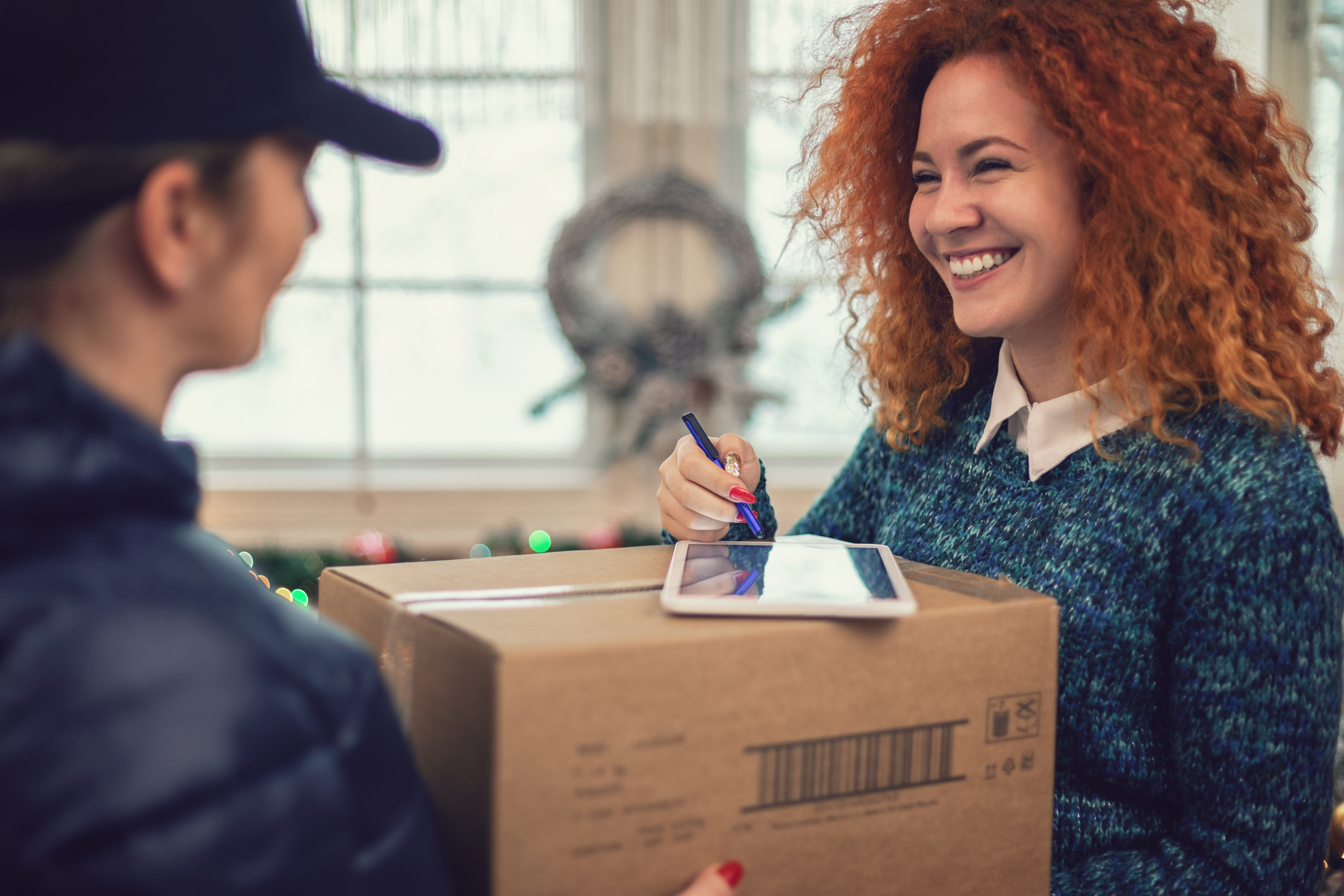Young beautiful girl accepting a package on Christmas