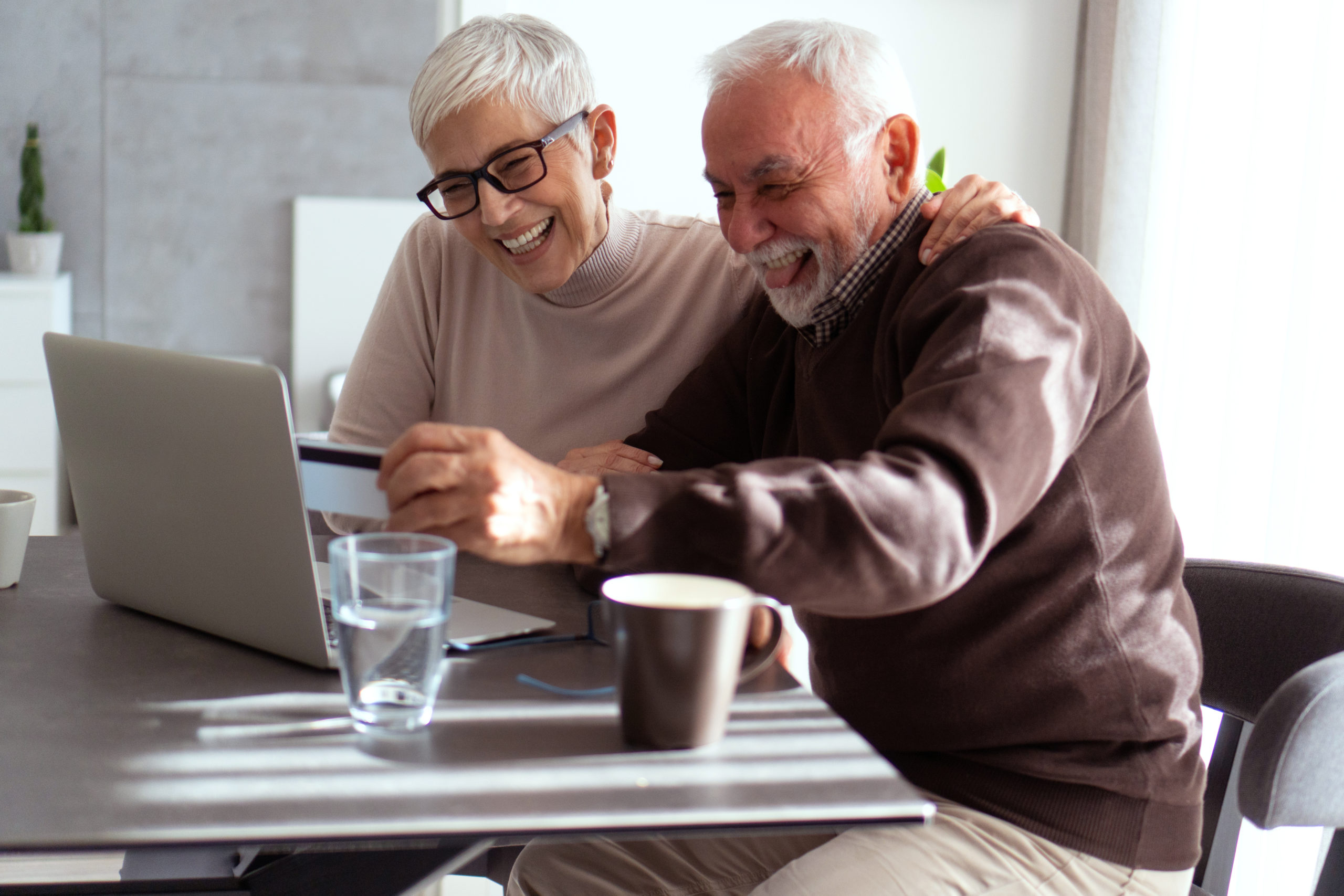 Senior people are shopping online by using laptop and credit card.