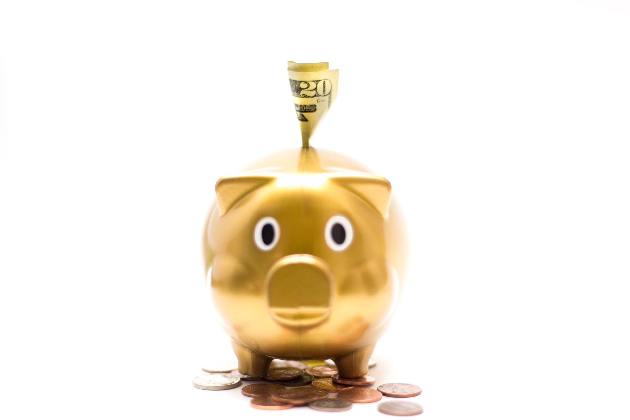 $20 bill in Gold Piggy Bank