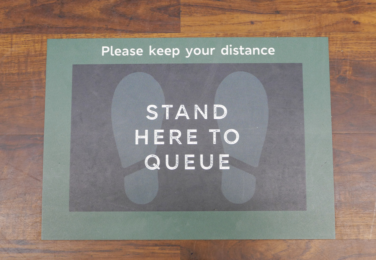 A food store queue instruction floor sticker, stuck to the wooden floor of the shop, during the Coronavirus pandemic. Customers are asked to stand two metres apart, using the footprint floor sticker as a distance marker within the store, while waiting near the checkout tills.