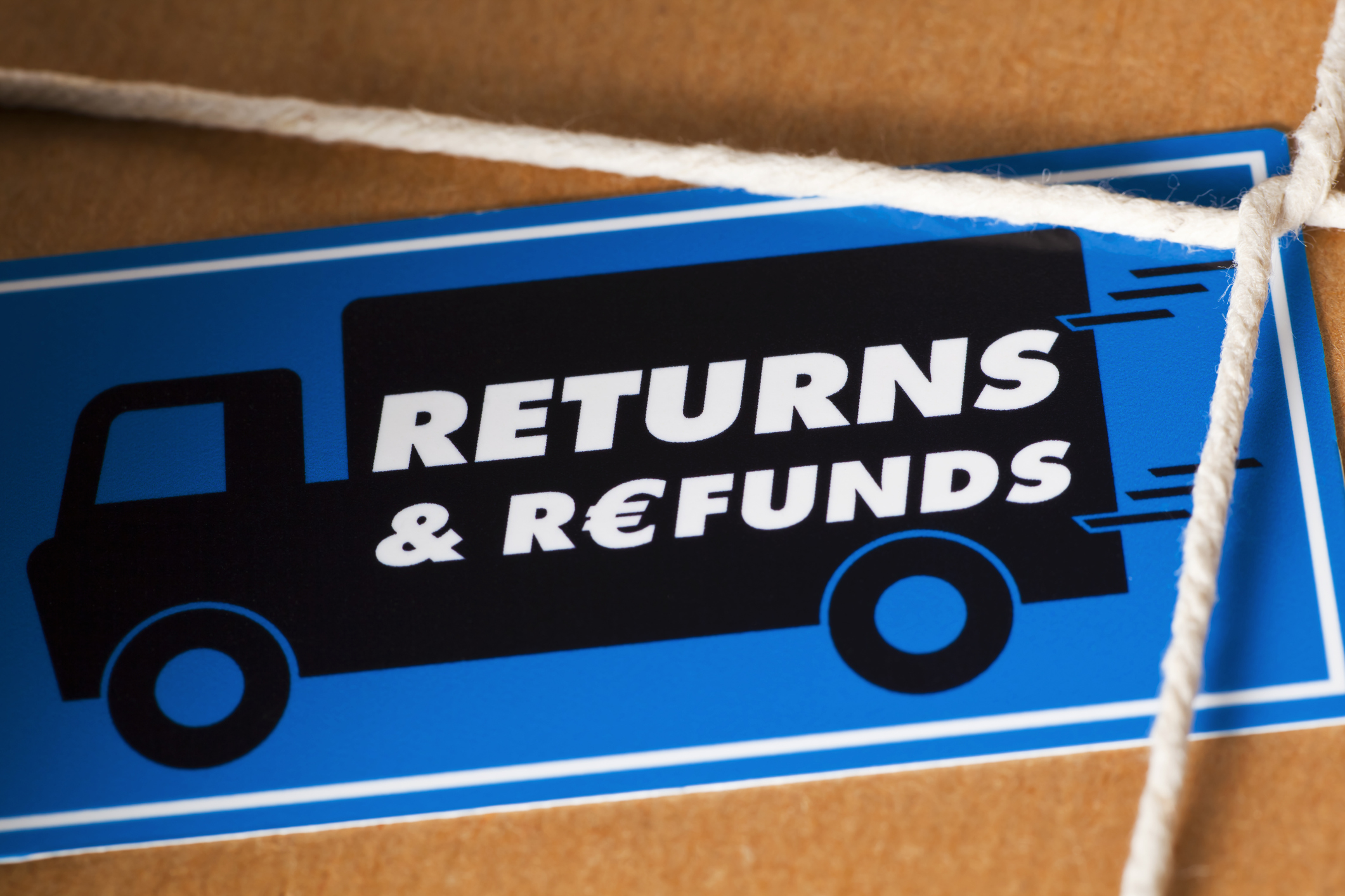Return the goods by a courier for a Euro Refund. Close up of a brown paper parcel, tied with string and a Return & Refunds sticker.